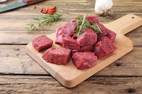 carne cruda manzo tagliato a cubi su tagliere sfondo legno rustico