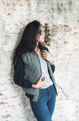 Beautiful young woman in Skinny jeans against an old brick wall