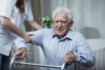 Physiotherapist helping disabled senior man