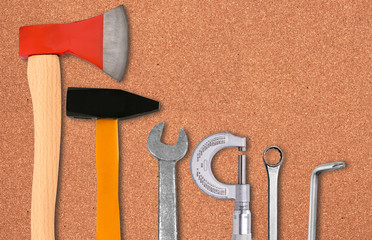 Ax, hammer, screwdriver and wrenches over cork background