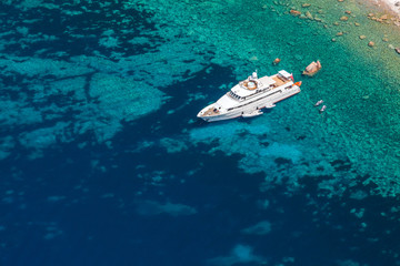 Luxury white pleasure yacht near rocky coast