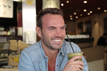 Handsome healthy man holding a cup of green vegetable juice and vegetables