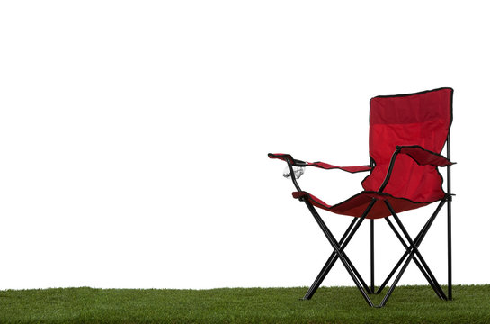 Folding camp chair on grass with white background