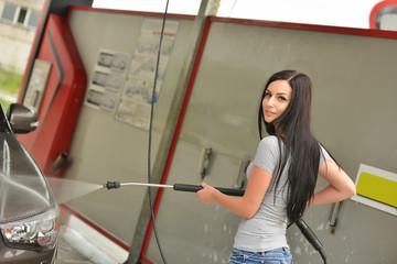Young woman washing the car smiling
