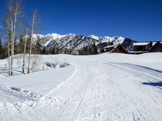 Groomed cross country ski trail with mountains, aspens and buildings