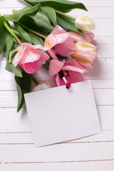 Bunch of fresh  spring  pink  tulips and empty tag  on white  pa