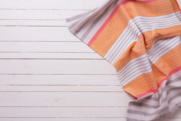 Orange  kitchen towel  on white wooden background.