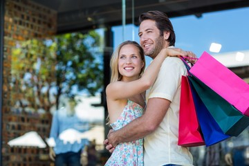 Smiling couple with shopping bags hugging