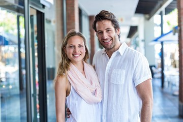 Smiling man putting arm around his girlfriend