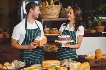 Smiling co-workers showing bread and cake