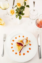 Cherry pie/Two slices of cherry pie in portion on a white plate in restaurant. Decorative restaurant table. Wine and flowers.