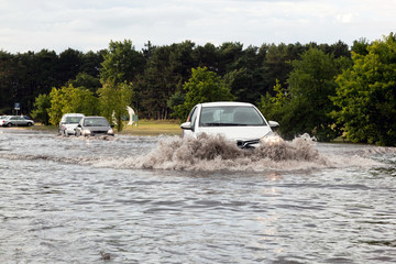 Cars trying to drive against flood on the street in Gdansk, Poland