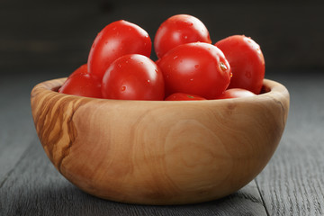 red cherry plum tomatoes in olive bowl on wood table