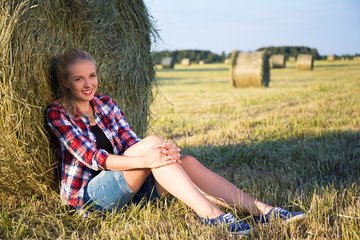 beautiful blonde woman sitting near haystack in field