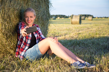 beautiful woman making selfie photo on smartphone in field with
