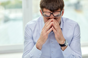 tired businessman with eyeglasses in office