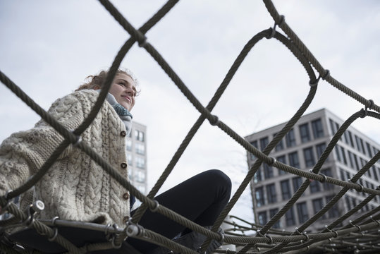 Low angle view of a young woman sitting on climbing net, Munich, Bavaria, Germany