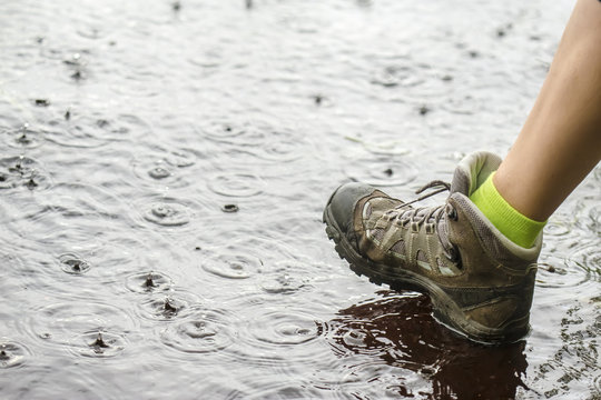 person in tourist waterproof hiking boots walking on water in the puddles in the rain