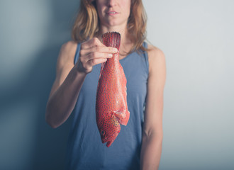 Young woman holding red fish