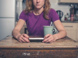 Young woman in kitchen with tea and smart phone