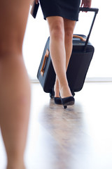 Hostess legs with luggage in airport.