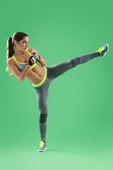 sportswoman in training, making side kick, her hands in front of
