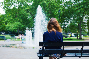 Young woman looking at fountain in park
