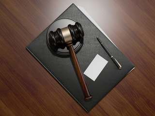 Wooden judges gavel and leather folder on the brown wooden background
