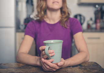 Young woman with cup in kitchen