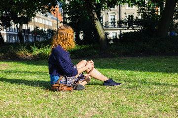 Young woman sitting on grass in park