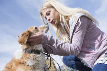 Low angle view of teenage girl kissing her dog, Munich, Bavaria, Germany