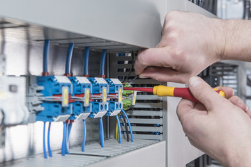 Close-up of electrician screwing cable in distribution fusebox, Munich, Bavaria, Germany