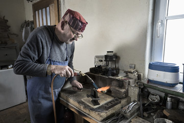 Senior male goldsmith melting and casting with blow torch at workshop, Bavaria, Germany