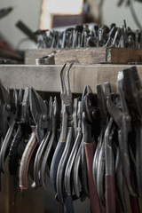 Close up of pliers hanging on wooden table