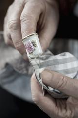 Senior female fashion designer wearing a thimble stitching in workshop, Bavaria, Germany
