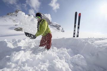 Man shovelling snow for bivouac camp, Tyrol, Austria