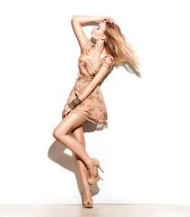 Fashion model girl dressed in short chiffon beige dress. Full length portrait