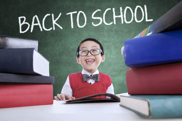 Fotobehang - Adorable boy back to school and smiling in class