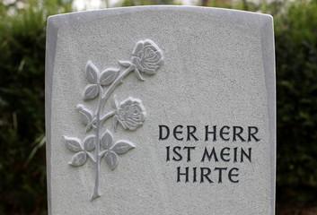 Grabstein mit eingemeisselter Rose und Schriftzug