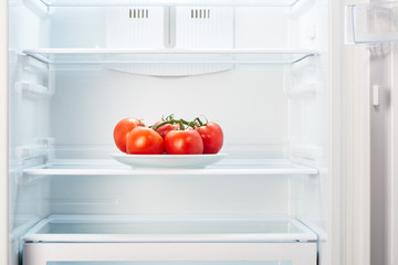 Branch of tomatoes on white plate in open empty refrigerator