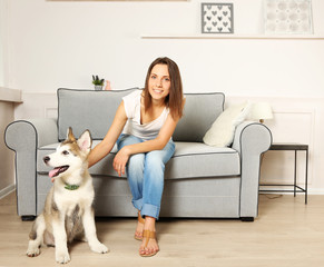 Portrait of young woman and her malamute dog in room