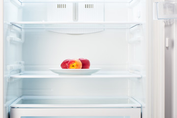 Peaches on white plate in open empty refrigerator