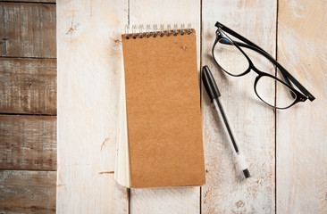 notepad,glasses and ink pen on the wooden