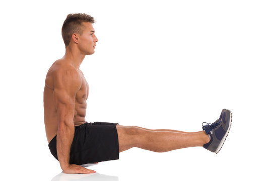 Calisthenics Workout. Muscular man sitting and holding legs above the ground. Full length studio shot isolated on white.
