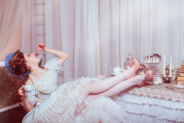 Indoors shot in the Marie Antoinette style. Woman eating red cherry.