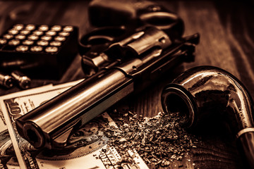Money and a gun with a box of ammunition with a pipe on a wooden table