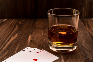Fototapete - Glass of whiskey and playing cards on the wooden table