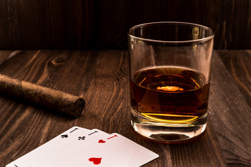 Wall Mural - Glass of whiskey and playing cards with cuban cigar on the wooden table