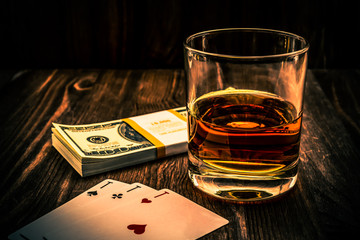 Fototapete - Glass of whiskey and playing cards with pack of dollars on the wooden table