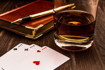 Fototapete - Glass of whiskey and playing cards with leather notebook on a wooden table